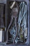 Plattången spikar och skruvar inahjälpmedelboox royaltyfri foto