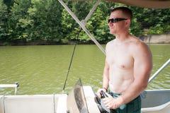 Platt halmhatt: Man som lotsar motorbåten Royaltyfri Bild