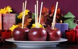 Platta av äpplen på pinnar som är klara att göras in i allhelgonaaftontrick eller äpplen för festkolakaramell Royaltyfri Bild