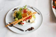 Platta av brien, parmesan, druvor, vinbär och såser royaltyfria foton