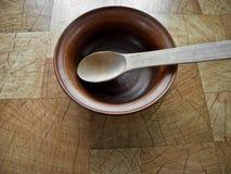 Platta av brun lera och en träsked på tabellen royaltyfri foto