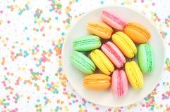 Platta av färgrika macarons på ljus festlig dekorbakgrund, söt confection arkivfoto