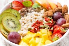platta av havremjölhavregröt med ny frukt och superfoods royaltyfri foto