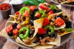 Platta av kryddiga fullastade mexicanska nachos royaltyfria foton