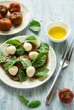 Platta av ny caprese sallad med svarta tomater, den mini- mozzarellaen och basilikasidor Arkivfoto