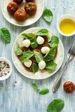 Platta av ny caprese sallad med svarta tomater, den mini- mozzarellaen och basilikasidor Arkivfoton