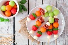 Platta av sommarfruktsteknålar på lantligt vitt trä arkivbilder