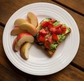 Platta av tomaten och avokadot på rostat bröd med Apple skivor Royaltyfri Bild