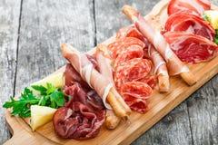 Platta för kallt kött för Antipastouppläggningsfat med grissinibrödpinnar, prosciuttoen, skivor skinka, knyckigt för nötkött, sal royaltyfria bilder