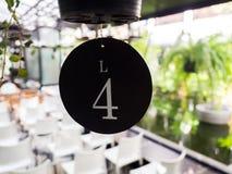 Platta för nummer fyra av tabellen i restaurang Arkivbilder