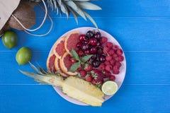 Platta för ny frukt på livlig blå bakgrund - ananas, kokosnöt, limefrukt Bästa sikt från ovannämnd fast utgift tropisk strandlivs arkivbilder