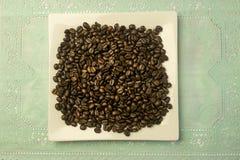 Platta för vit fyrkant med en hög av kaffebönor Arkivbilder