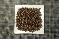 Platta för vit fyrkant med en hög av kaffebönor Arkivfoto