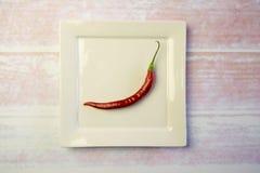 Platta för vit fyrkant med en röd peppar Arkivbilder