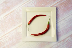 Platta för vit fyrkant med två röda peppar Royaltyfria Foton