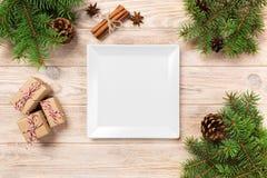 platta för vit fyrkant på en trätabell med julgarnering fyrkantig tom maträtt nytt år för begrepp arkivbild