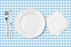 Platta, gaffel, kniv och servett över blå tableclot Arkivbilder