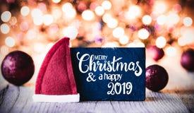 Platta, glad jul för kalligrafi och en lycklig 2019, Santa Claus Hat arkivfoton