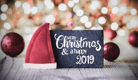 Platta, glad jul för kalligrafi och en lycklig 2019, Santa Hat royaltyfria bilder