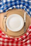 Platta, kniv och gaffel på skärbrädan arkivfoto