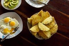 Platta med ananasskivor, stekte ägg och avokadot royaltyfri bild