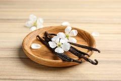 Platta med aromatiska vaniljpinnar och blommor fotografering för bildbyråer