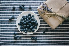 Platta med blåbär på en randig bordduk Arkivfoto