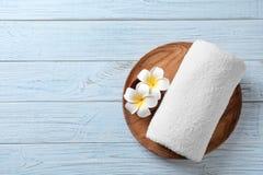 Platta med blommor och handduken på träbakgrund arkivbild