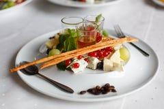 Platta med brieost, parmesan, druvor, vinbär och såser arkivbilder