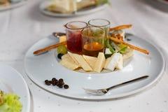 Platta med brieost, parmesan, druvor, vinbär och såser royaltyfri fotografi