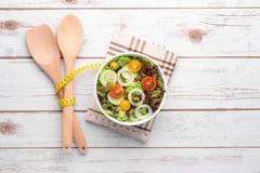 Platta med den nya sallad, kniven och gaffeln banta mat Arkivbilder