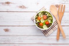 Platta med den nya sallad, kniven och gaffeln banta mat Royaltyfri Fotografi