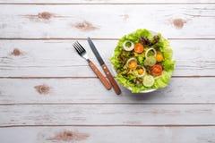 Platta med den nya sallad, kniven och gaffeln banta mat Arkivfoto