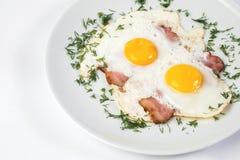 Platta med den stekte ägg-, bacon- och hönakorven arkivbild