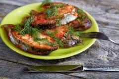Platta med den stekte fisken på en tabell Fotografering för Bildbyråer