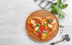 Platta med denformade pizza, ingredienser och kniven på träbakgrund arkivfoton
