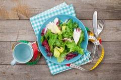 Platta med det nya sallad, måttbandet, koppen, kniven och gaffeln banta arkivbilder