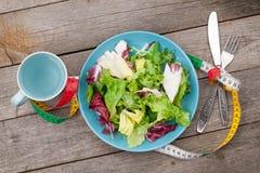 Platta med det nya sallad, måttbandet, koppen, kniven och gaffeln banta Royaltyfri Bild