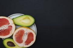 Platta med exotiska frukter som står på den totalt svarta tabellen, bästa sikt, kopieringsutrymme royaltyfri fotografi