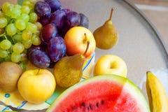 Platta med frukter - äpplen, päron, plommoner, druvor sund begreppsmat arkivfoto