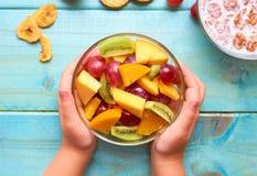 Platta med fruktsallad i händerna av barnet arkivfoton