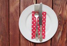 Platta med gaffeln, kniven och servetten royaltyfri bild