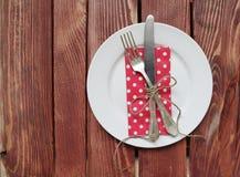 Platta med gaffeln, kniven och servetten royaltyfri foto