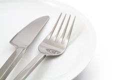 Platta med gaffeln och isolerad kniv Arkivfoto