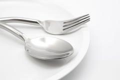 Platta med gaffeln och skeden Fotografering för Bildbyråer