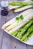 Platta med gröna och vita sparris och kryddor Arkivbild