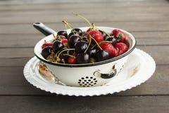 Platta med jordgubbar och söta körsbär Arkivbilder