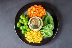 Platta med kål, morötter, havre och spenat ?ta som ?r sunt arkivfoton