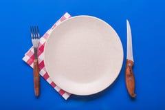 Platta med kniven och gaffeln Fotografering för Bildbyråer