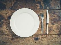 Platta med kniven och gaffeln arkivfoto